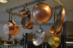CopperKitchen Cookware. Vintage pots and pans copper kitchen cookware on an overhead rack stock photo