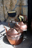 Copperware at an old fireplace. Copperware at a fireplace royalty free stock images