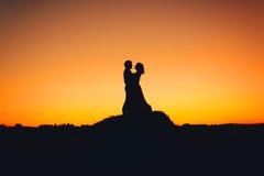 Coppia abbracciare sui precedenti del tramonto arancio Fotografie Stock