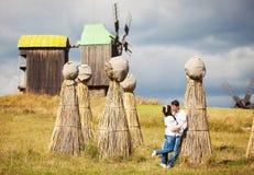 Coppia baciare sul campo con i pacchi di paglia Fotografie Stock Libere da Diritti