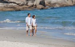 Coppia camminare sulla spiaggia sotto il sole Fotografie Stock Libere da Diritti