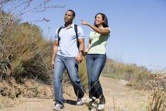 Coppia camminare sulle mani della holding del percorso e sorridere Immagini Stock