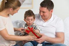 Coppia dare il regalo al loro piccolo figlio nel salone immagini stock