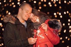 Coppia divertiresi con le stelle filante nella notte della città dell'inverno fotografia stock libera da diritti
