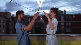 Coppia divertiresi l'ondeggiamento con le candele del fuoco d'artificio e la tostatura con il champagne archivi video