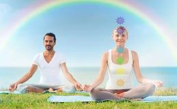 Coppia fare l'yoga nella posa del loto con sette chakras immagini stock libere da diritti