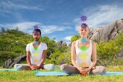 Coppia fare l'yoga nella posa del loto con sette chakras fotografie stock libere da diritti