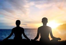 Coppia fare l'yoga nella posa del loto sopra il tramonto del mare immagini stock libere da diritti