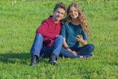 Coppia gli adolescenti che si siedono sul prato inglese verde con uno smartphone immagini stock
