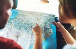 Coppia gli amici dei pantaloni a vita bassa che guardano ed indichi il dito sulla mappa di navigazione di posizione in automobile fotografie stock libere da diritti