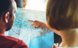 Coppia gli amici dei pantaloni a vita bassa che guardano ed indichi il dito sulla mappa di navigazione di posizione in automobile fotografie stock
