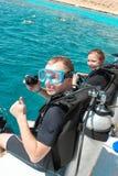 Coppia gli operatori subacquei che preparano tuffarsi dalla barca il giorno di estate fotografia stock libera da diritti
