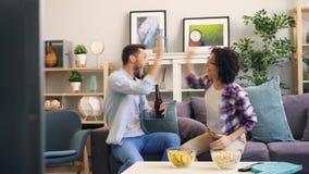 Coppia gli sport di sorveglianza sulla TV che sostiene poi fare alto--cinque ed abbracciare video d archivio