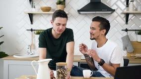 Coppia gli uomini bei gay stanno sedendo dietro il tavolo da cucina qualcosa che parlano per durante il caffè bevente alla cucina archivi video