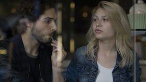 Coppia godere della loro prima data che parla e che mangia il gelato in un pub della caffetteria archivi video