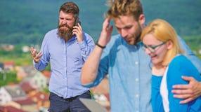 Coppia i colleghi che flirtano mentre capo occupato con la conversazione mobile Coppie divertendosi mentre navigazione in Interne immagine stock libera da diritti