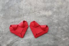 coppia i cuori di carta rossi pieganti sulla parete del cemento per il picchiettio del biglietto di S. Valentino Fotografia Stock