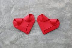 coppia i cuori di carta rossi pieganti sulla parete del cemento per il picchiettio del biglietto di S. Valentino Immagini Stock