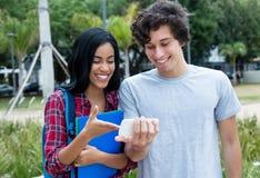 Coppia i giovani adulti del aof che guardano il film sul telefono cellulare Immagine Stock
