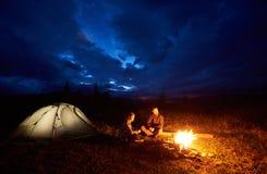 Coppia i turisti della donna e dell'uomo che hanno un riposo notturno che si accampa nelle montagne sotto il cielo nuvoloso immagini stock libere da diritti
