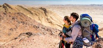 Coppia i viaggiatori con zaino e sacco a pelo dei turisti che stanno la cresta del picco di montagna del deserto immagini stock libere da diritti