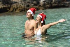Coppia il bagno sulla spiaggia sulle feste di natale Immagini Stock