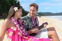 Coppia il divertimento sulla spiaggia che gioca le ukulele sulle Hawai Fotografia Stock