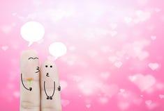 Coppia il fiore della tenuta del dito e la scatola di chiacchierata sulle sedere del cuore di rosa del bokeh Fotografia Stock