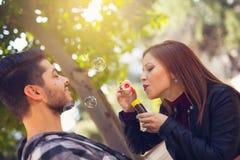 Coppia il rilassamento nel parco con il ventilatore della bolla Il tempo di primavera… è aumentato foglie, sfondo naturale Immagine Stock Libera da Diritti