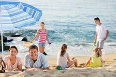Coppia il rilassamento sulla spiaggia mentre i loro bambini che giocano i giochi attivi Immagini Stock