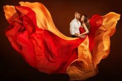 Coppia il ritratto di bellezza, uomo e donna di sogno in vestito d'ondeggiamento come fiamma su vento immagini stock