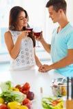 Coppia il tintinnio i loro vetri di vino rosso nella cucina Fotografia Stock