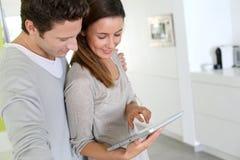 Coppia il togeteher diritto a casa con la compressa in mani Fotografia Stock
