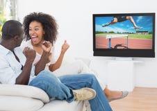 Coppia incoraggiare mentre guardano la corsa di transenna sulla televisione fotografia stock