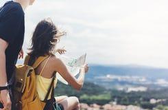 Coppia insieme la mappa turistica della tenuta e di sguardo dei pantaloni a vita bassa sul viaggio, avventura di concetto di stil fotografia stock libera da diritti