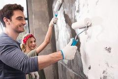 Coppia insieme la parete della pittura, concetto domestico del rinnovamento immagini stock