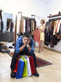 Coppia l'acquisto con le borse stanche e annoiate dell'uomo della tenuta ed il vestito di ricerca felice dalla donna Immagini Stock