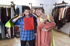 Coppia l'acquisto con le borse stanche e annoiate dell'uomo della tenuta ed il vestito di ricerca felice dalla donna Fotografia Stock