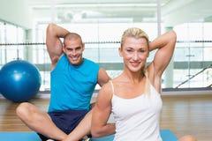 Coppia l'allungamento delle mani dietro indietro nella classe di yoga Fotografie Stock Libere da Diritti