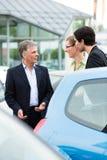 Coppia l'esame dell'automobile sull'iarda del commerciante Immagine Stock Libera da Diritti