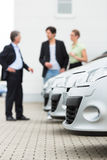 Coppia l'esame dell'automobile sull'iarda del commerciante Fotografie Stock