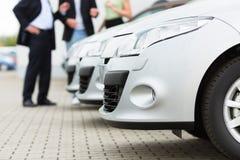 Coppia l'esame dell'automobile sull'iarda del commerciante Immagini Stock
