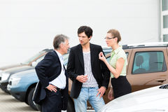 Coppia l'esame dell'automobile sull'iarda del commerciante Fotografie Stock Libere da Diritti