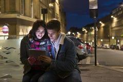 Coppia l'esame della compressa digitale nella città Fotografie Stock Libere da Diritti