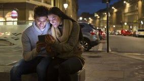 Coppia l'esame della compressa digitale nella città Immagine Stock