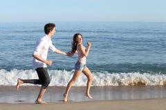Coppia l'inseguimento e correre sulla riva della spiaggia fotografia stock