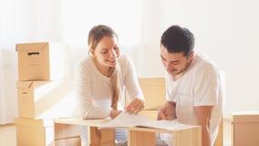 Coppia l'installazione della mobilia nella nuova casa con l'istruzione stock footage