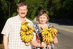 Coppia l'uomo e la donna che sorridono e che giudicano mascolino delle banane Fotografia Stock