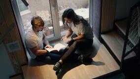 Coppia l'uomo e la donna per leggere e discutere il libro che si siede sulle scale dalla finestra nella casa video d archivio