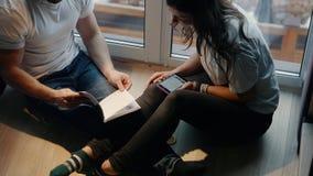 Coppia l'uomo e la donna per leggere e discutere il libro che si siede sulle scale dalla finestra nella casa donna con il telefon video d archivio